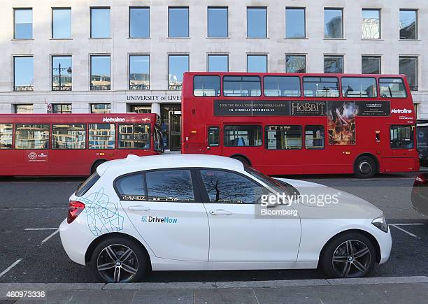 Red London buses stand parked beyond a BMW 1 series automobile part of the DriveNow carsharing venture between Bayerische Motoren Werke AG and Sixt...