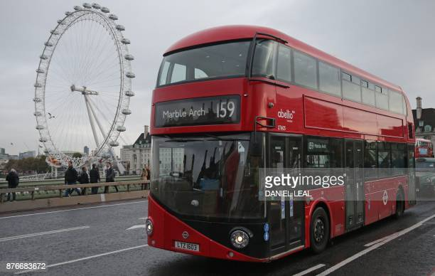 A red London doubledecker bus passes the London Eye as it is driven over Westminster Bridge in central London on November 20 2017 London's caffeine...