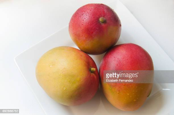 Red mangoes on plate.