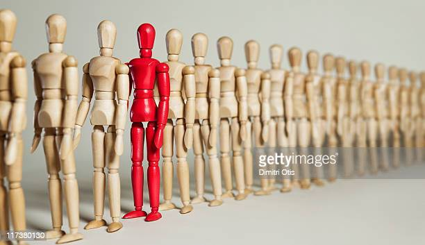 Red mannequin stands in a long line of wooden ones