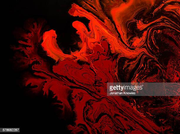 Red marbling paint on black background