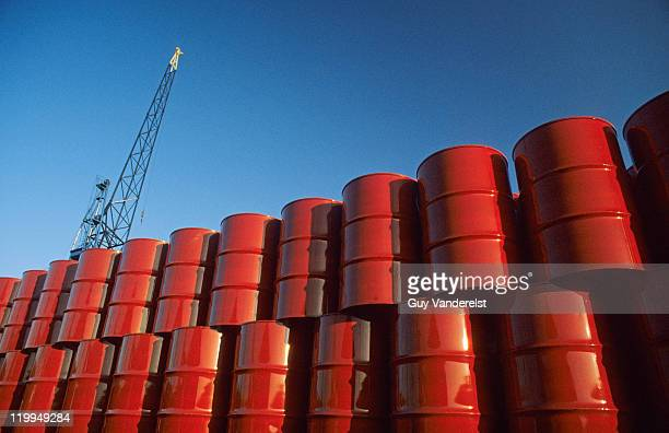 Red metal barrels against blue sky.