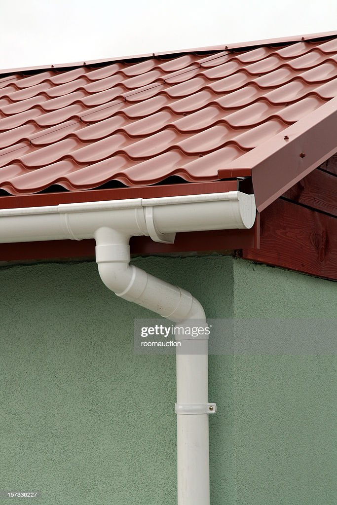 Red metal roof with white rain gutters : Stock Photo