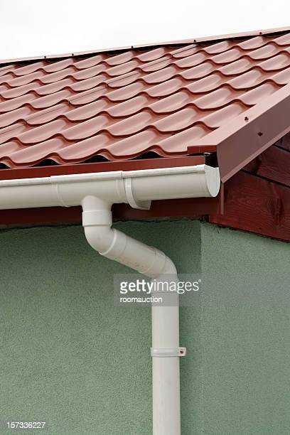 Red metal roof with white rain gutters
