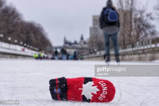 red mitt and the winter view of the rideau canal skateway in ottawa during winterlude 2019. the world's longest skating rink is enjoyed by many skaters. - mitten stock pictures, royalty-free photos & images