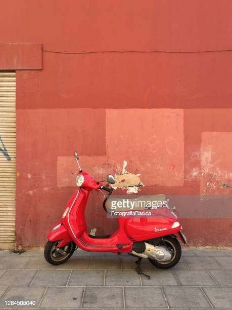 red motor scooter parked on the sidewalk - vespa brand name stock pictures, royalty-free photos & images