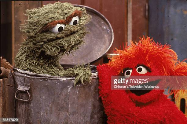 A red muppet visits Oscar the Grouch inside his garbage can in a scene from the children's television program 'Sesame Street' 1980s