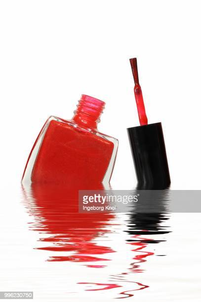 Red nail polish bottle with brush in water