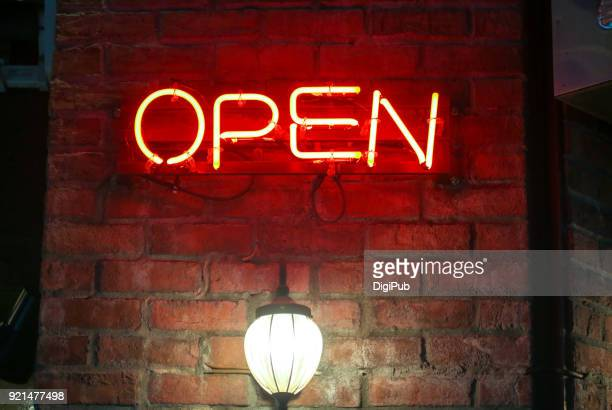 red neon open sign on red brick exterior wall in the night - neon letters stock photos and pictures