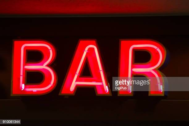 """Red neon sign """"BAR"""" in the night"""