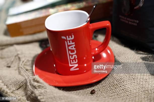 A red Nescafe branded coffee cup stands on display at the Nestle SA headquarters in Vevey Switzerland on Thursday Feb 15 2018 Since taking over about...