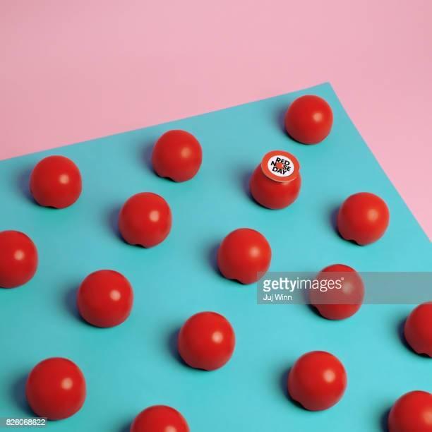 red noses arranged on a blue background - nariz de payaso fotografías e imágenes de stock