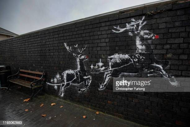 Red noses have appeared on Banksy's Birmingham homeless reindeer mural , which has also been fenced off to protect the artwork, on a railway bridge...