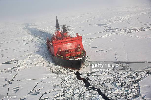 a red nuclear ice breaker ship in iceberg water - ijsschots stockfoto's en -beelden