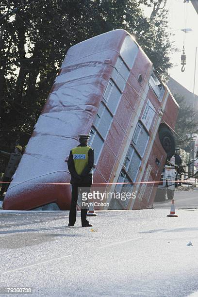 Red number 26 double-decker bus, operated by Eastern Counties Buses Ltd., lies stuck in a hole after sinking into an old chalk mine on Earlham Road...