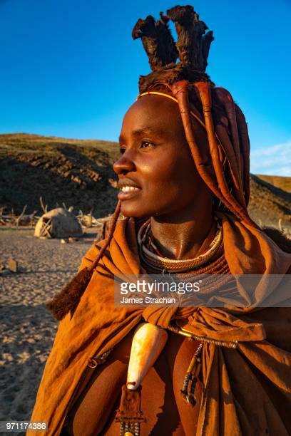 red ochred, bare breasted himba woman in traditional dress looking into the distance, in the evening light, puros village, near sesfontein, namibia (model release) - himba stock-fotos und bilder