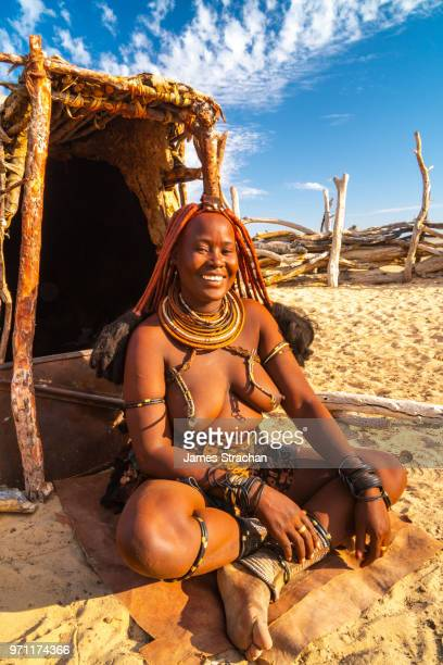 Red ochred, bare breasted Himba woman in traditional dress sitting outside her hut, with big smile, Puros Village, near Sesfontein, Namibia (Model Release)