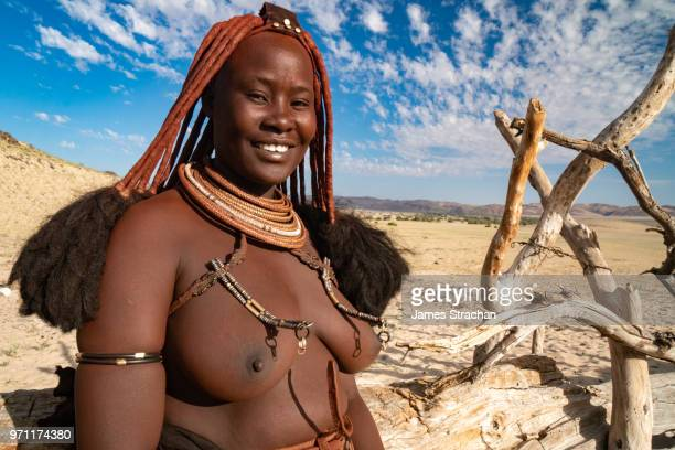 Red ochred, bare breasted Himba woman in traditional dress with big smile by external fence of Puros Village, near Sesfontein, Namibia (Model Release)