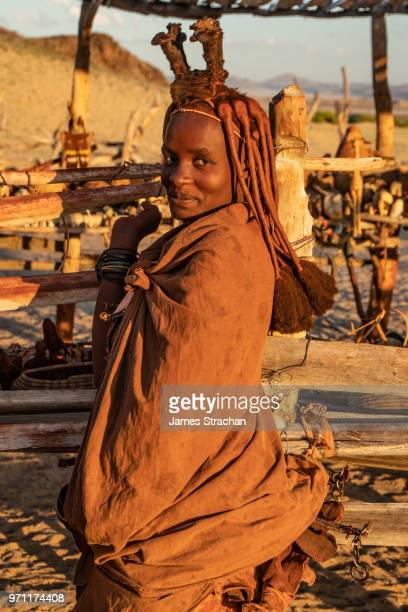red ochred himba woman in traditional dress smiling coyly, in the evening light, puros village, near sesfontein, namibia (model release) - himba photos et images de collection