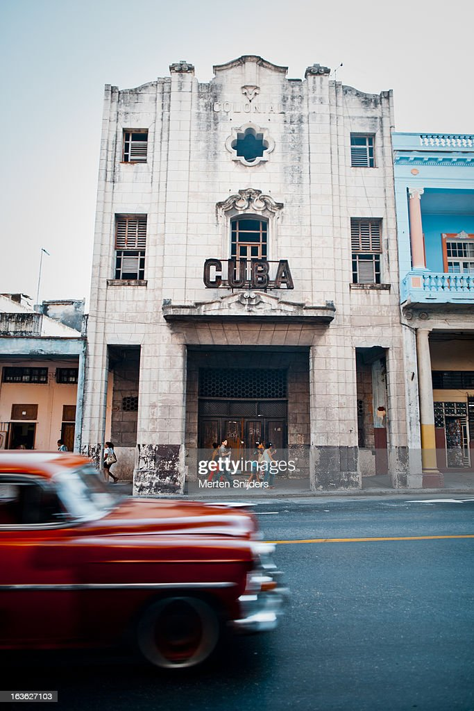 Red oldtimer car passing Cuba sign : Stockfoto