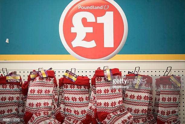 A red one pound logo sits above a display of seasonal Christmas stockings inside a Poundland discount store operated by Poundland Group Plc in the...
