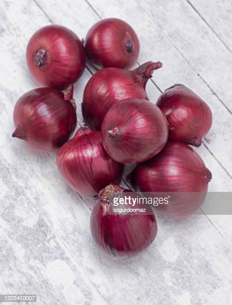 red onions on wood background - red onion stock pictures, royalty-free photos & images