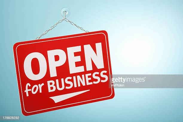Red open for business sign hanging in a window