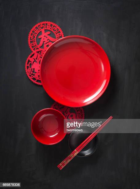 Red oriental style eating utensils on black textured background.
