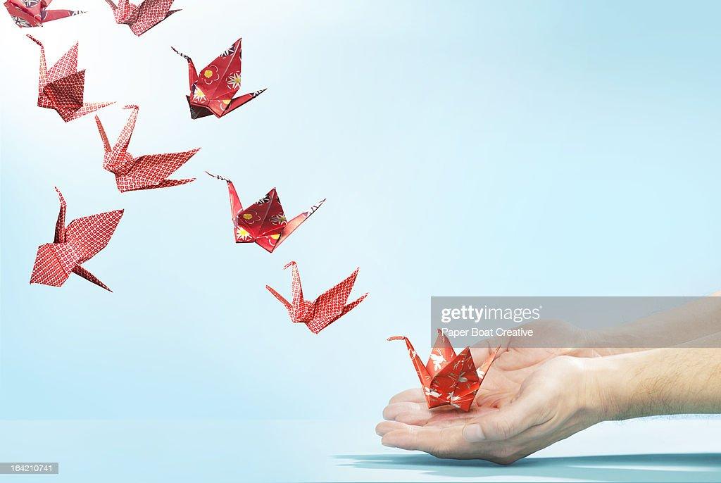 Red origami cranes flying away from hands : Foto de stock
