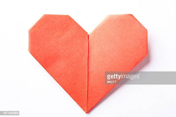 A red origami heart on a white background