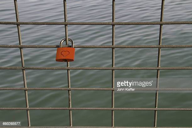 Red padlock on bridge