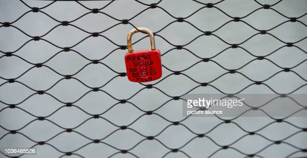 A red padlock with the lettering 'Fuck the World Be Wild Be Free YOLO 2013' hangs on the wir emesh of a bridge across the Isar in Munich Germany 11...