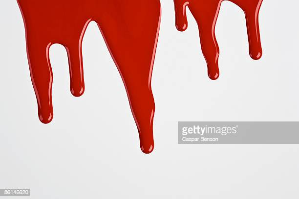 Red paint dripping down a white wall