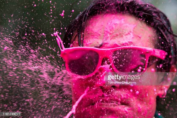 Red paint is sprayed onto the face of a participant during the Color Me Rad Tokyo 2019 at the Ajinomoto Stadium on July 13 2019 in Tokyo Japan...