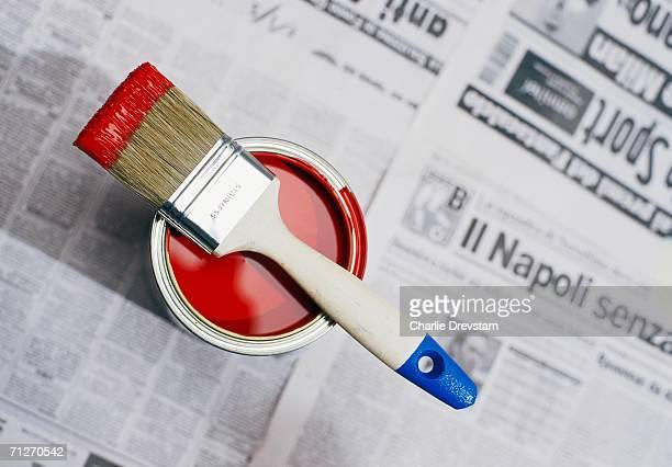 red paint on a newspaper. - farbeimer stock-fotos und bilder