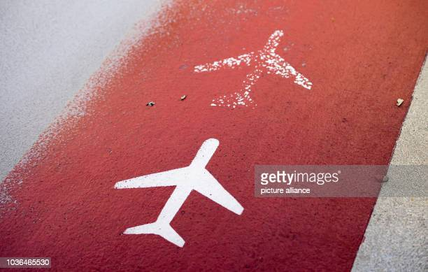 A red painted walkway with coloured airplanes guides the way towards departure terminal 2 at the airport in Munich Germany 9 November 2015 Photo...