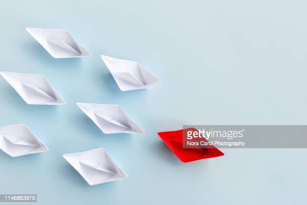 red paper boat followed by white paper - strategie stock-fotos und bilder