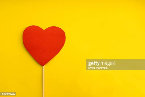 red paper heart on yellow background - heart month stock photos and pictures