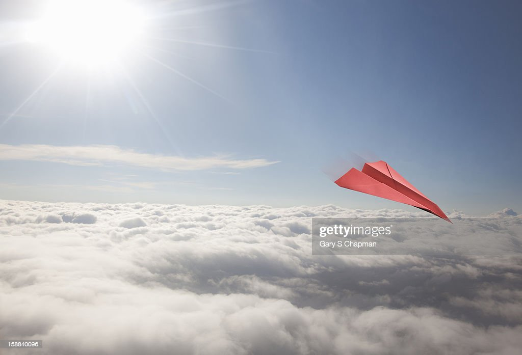 Red paper plane flying high above clouds : Stock Photo