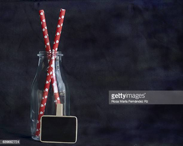 Red paper straws with shapes heart in empty glass bottle against abstract background. Subject captured againt soft window lighting an copy space
