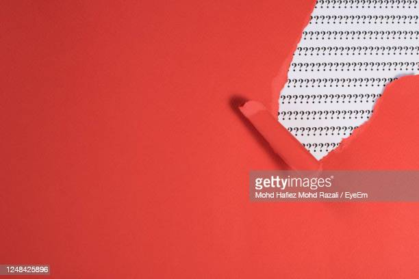 red paper teared revealing question mark on white paper. - q and a stock pictures, royalty-free photos & images