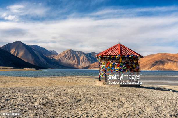 Red pavilion in Mountains and Pangong tso (Lake). It is huge and highest lake in Ladakh and blue sky in background, it extends from India to Tibet. Leh, Ladakh, Jammu and Kashmir, India