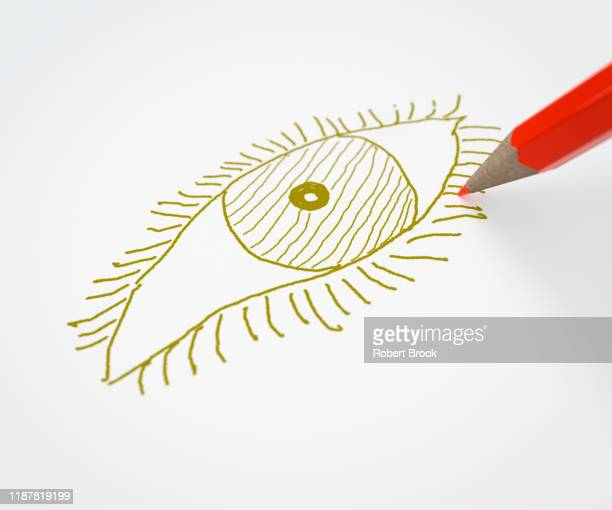 red pencil drawing an eye in a different colour - colorblind artist in full color stockfoto's en -beelden