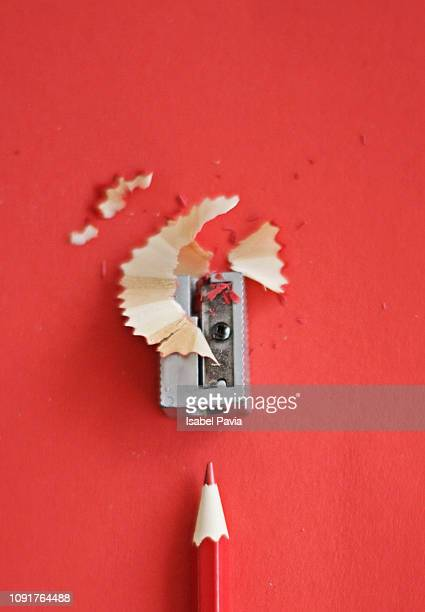 red pencil with sharpening shavings on red background - school supplies stock pictures, royalty-free photos & images