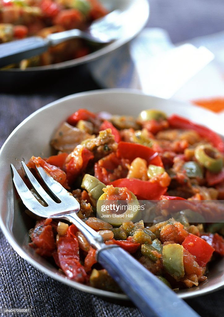 Red pepper and olive dish in bowl with fork, close-up : ストックフォト