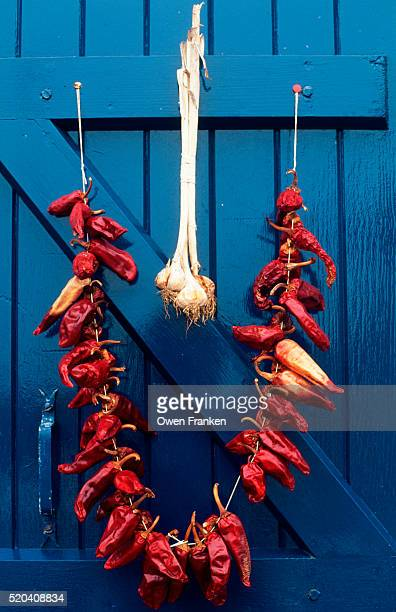 Red Peppers and Garlic Hang on a Blue Door