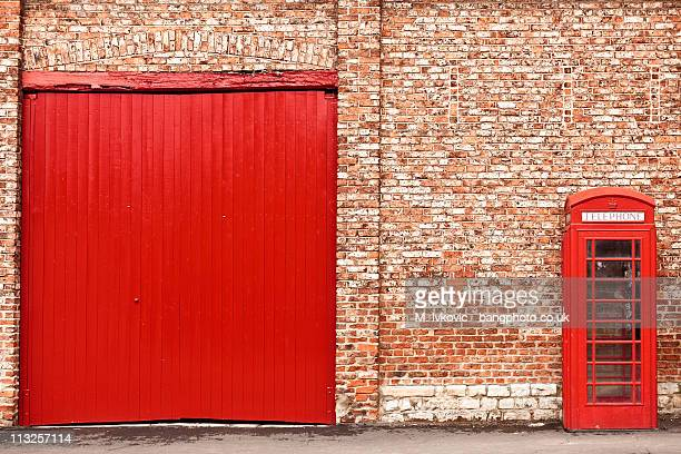 Red phonebox and door against red brick wall