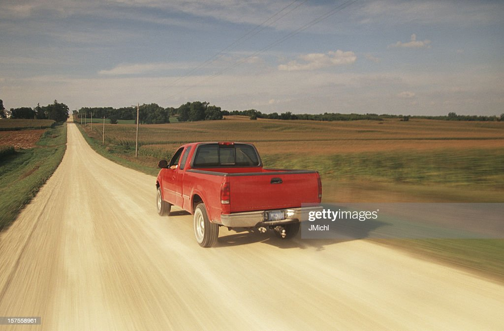 Red Pick Up Truck Traveling Down a Dusty Midwest Road. : Stock Photo