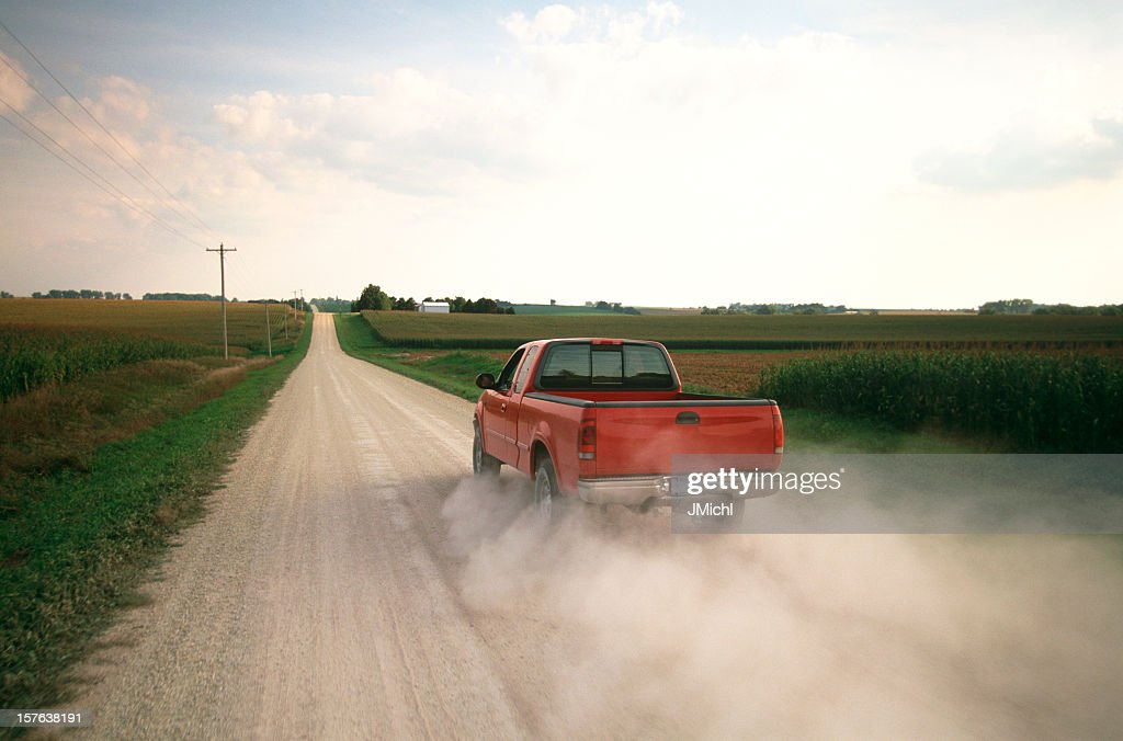 Red Pick Up Truck Traveling Down A Dusty Midwest Road