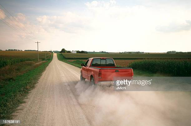 Red Pick Up Truck Traveling Down a Dusty Midwest Road.